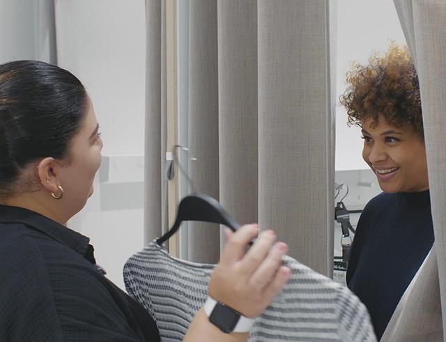 Eine Mitarbeiterin von Ulla Popken berät eine Kundin.