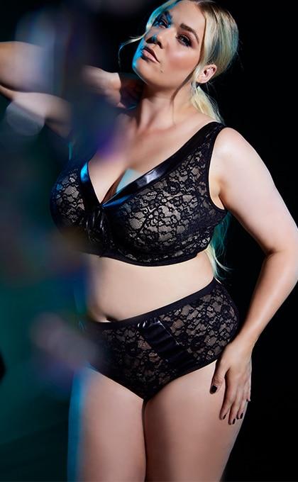 Frau mit blondem Haar mit erotischem Bralette und Taillenslip in schwarzer Lederoptik