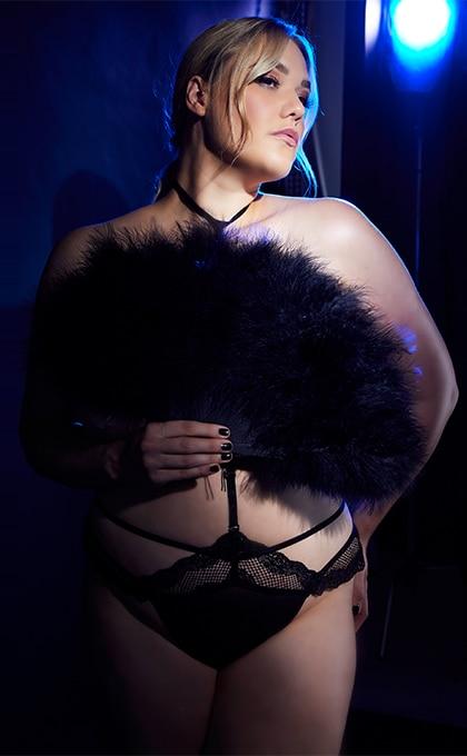 Frau im schwarzen String mit Choker mit einem Federfächer vor dem Oberkörper haltend